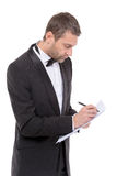 Handsome man in a bow tie writing notes Royalty Free Stock Photography