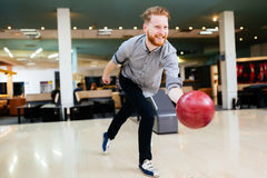 Handsome man bowling. In club and throwing ball Royalty Free Stock Image
