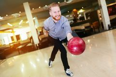 Handsome man bowling. In club and throwing ball Stock Photo