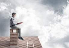 Handsome man on brick roof against cloud scape reading book Stock Photos