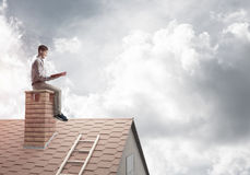 Handsome man on brick roof against cloud scape reading book Stock Photo