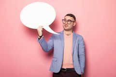Handsome man in bright jacket with speech bubble. Portrait of handsome businessman in pink jumper, blue jacket and glasses holds blank paper thinking speech Royalty Free Stock Images