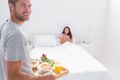 Handsome man bringing breakfast to his wife Royalty Free Stock Photos