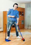 Handsome man with broom and dustpan at home Royalty Free Stock Image