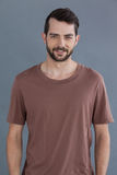 Handsome man in brown t-shirt. Portrait of a handsome man in brown t-shirt against grey background stock images