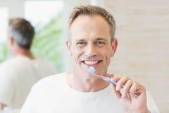 Handsome man brushing his teeth Stock Photos