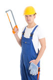 Handsome man in builder uniform and helmet with manual saw isola Stock Images