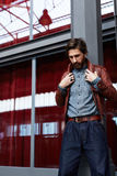 Handsome man in the burgundy jacket and jeans at the mall. Portrait of aged fashionable hipster man with beard posing indoors adjusting his leather jacket royalty free stock images