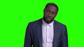 Handsome man in business suit looking at his watch. Afro-american guy in formal wear waiting for somebody on green screen. Punctuality and accuracy concept stock video footage
