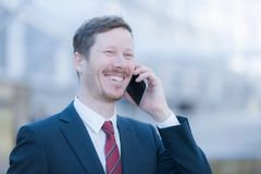 Very happy man making a phone call. Handsome man in business suit is making a phone call, he`s very happy and smiling Royalty Free Stock Photos