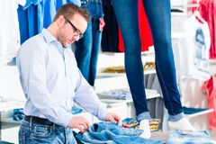 Handsome Man buying blue jeans in shop or store Stock Photos