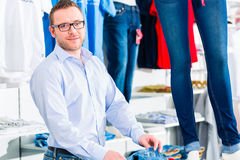 Handsome Man buying blue jeans in shop Royalty Free Stock Images