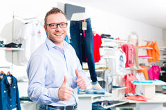 Handsome Man buying blue jeans in shop Stock Photography