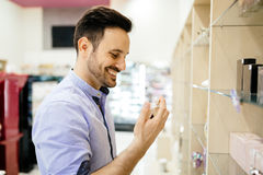 Handsome man buying fragrances. And perfumes Royalty Free Stock Photo