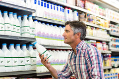 Handsome man buying milk. Side view of handsome man buying milk Royalty Free Stock Photos