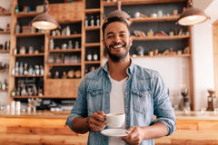 Handsome man in a cafe with cup of coffee. Portrait of handsome young man standing in a cafe with a cup of coffee. Smiling young guy having coffee in a Royalty Free Stock Images