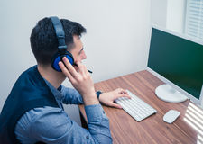 Handsome man in call center with headphones Stock Photos