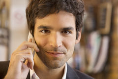 Handsome man calling with a cell phone in coffee bar, looking ca Royalty Free Stock Images