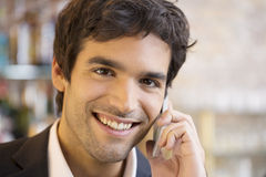 Handsome man calling with a cell phone in coffee bar, looking ca Stock Photos