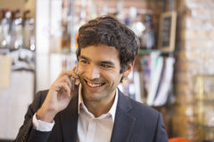 Handsome man calling with a cell phone in coffee bar Stock Image