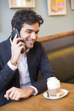 Handsome man calling with a cell phone in coffee bar Stock Photography