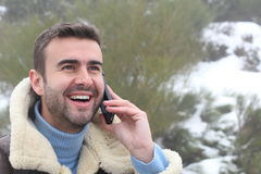 Handsome man calling by phone outdoors in the winter Royalty Free Stock Photos