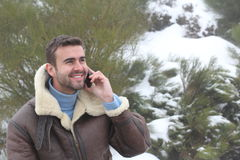 Handsome man calling by phone outdoors in the winter with copy space Royalty Free Stock Photo