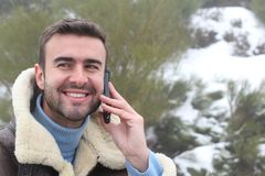Handsome man calling by phone outdoors in the winter Stock Photography