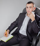 Handsome man calling and sitting on the chair Royalty Free Stock Images