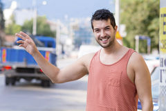 Handsome man calling taxi cab on the street Stock Photography