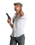 Handsome man in cap with a gun. On a white background Stock Photography