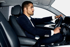 Handsome man in the car. Luxury life. Handsome young man in costume inside the car royalty free stock photos