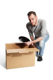 Handsome man with cardboard box and plates Stock Images