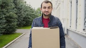 Handsome man carrying a cardboard box and walking outdoor.  stock footage