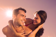 Handsome man carrying his girlfriend on his back Stock Image