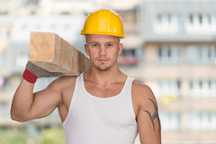 Handsome Man Carrying Wood Planks Stock Photo