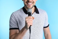 Handsome man in casual clothes holding microphone stock image