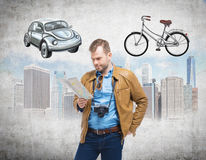 A handsome man in casual clothes holds a map and thinks about the most suitable way for travelling or commuting in the city. Sketc Stock Photos