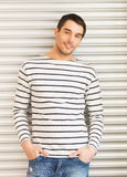 Handsome man in casual clothes leaning to wall stock images