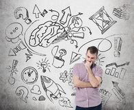 A handsome man in casual clothes is thinking about business development. A brainstorm sketch is drawn on the concrete wall. Royalty Free Stock Photos