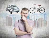 A handsome man in casual shirt is trying to chose the most suitable way for travelling or commuting in the city. Sketches of a car Royalty Free Stock Photos