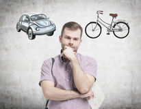 A handsome man in casual shirt is trying to chose the most suitable way for travelling or commuting. Two sketches of a car and a b Stock Photo