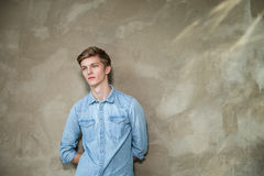 Handsome man in casual wear standing against grey Stock Photos