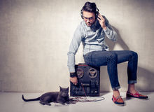 Handsome man and cat listening to music on a magnetophone