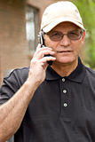 Handsome Man on Cell Phone. Handsome mature man wearing baseball cap while talking on cell phone Royalty Free Stock Images