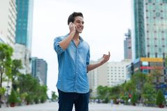 Handsome man cell phone call smile outdoor city. Street, Young attractive businessman casual blue shirt talking Stock Photo