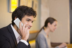 Handsome man on cell phone in coffee bar Royalty Free Stock Image