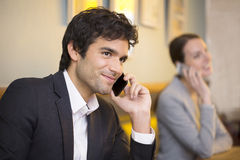 Handsome man on cell phone in coffee bar Stock Photo