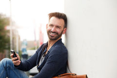 Handsome man with cell phone sitting by a wall outdoors Stock Image
