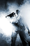 Handsome man with chainsaw. And abstract smoke stock image